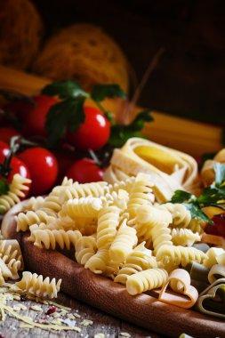 Italian food: pasta spiraline, herbs, tomatoes