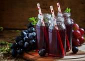 Fotografie Dark grape juice in glass bottles with straws