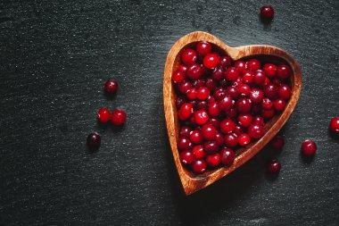 Fresh cranberries in a wooden bowl in the shape of a heart