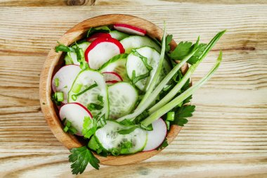 Spring salad with radishes, cucumbers, green onions and herbs