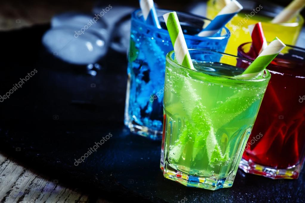 Colorful cocktails with straws on a dark background