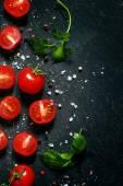 Nakrájíme cherry rajčátka na černém pozadí