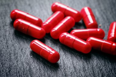 Red pills in capsules of anemia on a black table