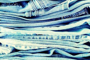 Denim background, some jeans trousers on the table