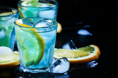 Blue cocktail with ice cubes and slices of orange