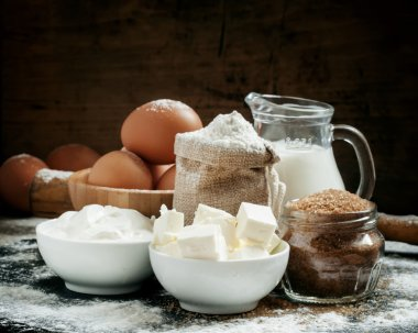 Baking ingredients: milk, butter, flour, sugar, eggs and rolling pin