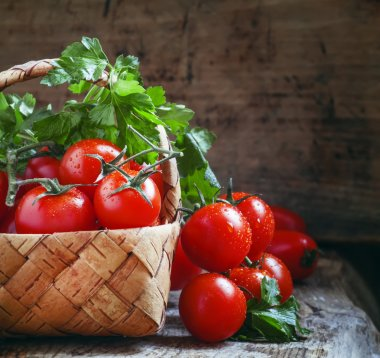 Cherry tomatoes and parsley in wicker basket