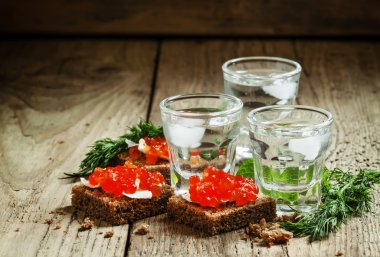 Cold Russian vodka with ice and small snacks sandwiches with caviar