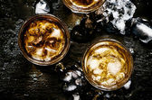 Cold whiskey in glasses with crushed ice