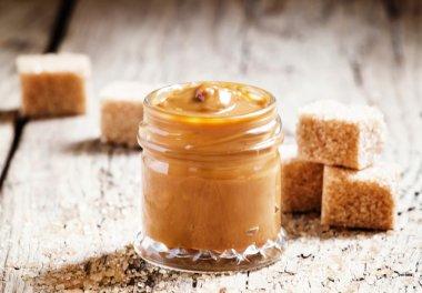 Sweet liquid caramel in a small jar and brown cane sugar