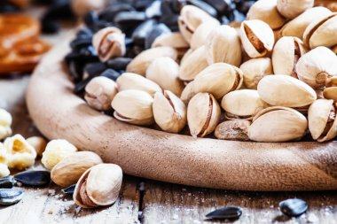 Salted pistachios on a vintage wooden background