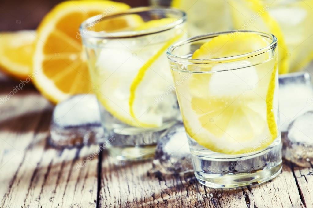 Cold Russian vodka with lemon and ice in shot glasses