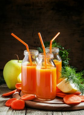 Carrot apple smoothie in glass bottles