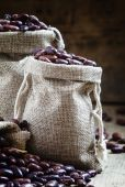 Photo Dry beans in burlap sacks on old wooden background