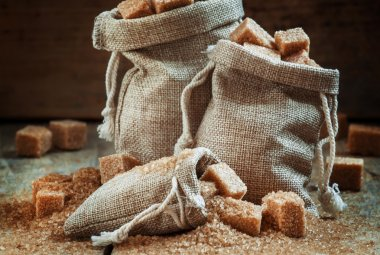 Cane brown sugar cubes and crystals in burlap sacks