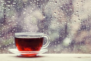 Cup of hot black tea on the blurred background of wet window