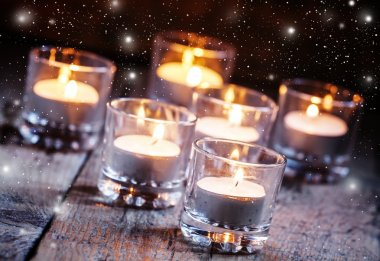 Burning small candles in glass candlesticks