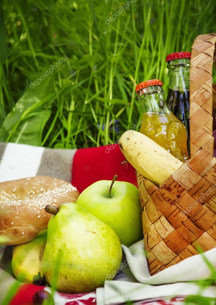 Picnic Basket with fruits and drinks on the meadow on a background