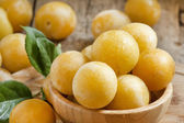 Ripe juicy yellow plums in a wooden bowl