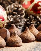 Fotografie Chocolate truffles, sprinkled with cocoa powder, red Christmas balls