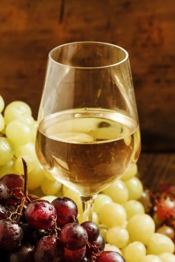 White wine in a glass and green and red grapes