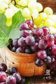 Lila kerek érett szőlőből készült, egy fonott kosárban