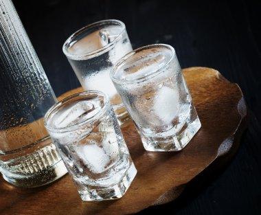 Bottle of vodka and glasses full of ice