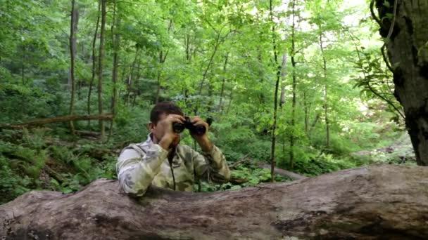muž s dalekohledem v lese. usilovat, aby lovili. sedět v záloze. Hledejte řešení. Sledujte od postranní čáry. partyzáni v záloze. Při pohledu dalekohledem. Najdete řešení. papala