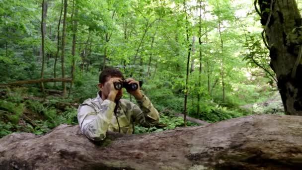 muž s dalekohledem v lese. usilovat, aby lovili. sedět v záloze. Hledejte řešení. Sledujte od postranní čáry. partyzáni v záloze. Při pohledu dalekohledem. papala