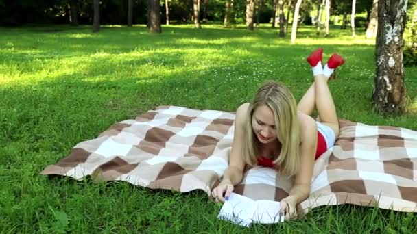 Girl in the park reading a book. Girl has a rest with a book on nature. Woman reading while lying on the grass.  Activities in the park and pleasant hobby. Student engaged literature.Summer day