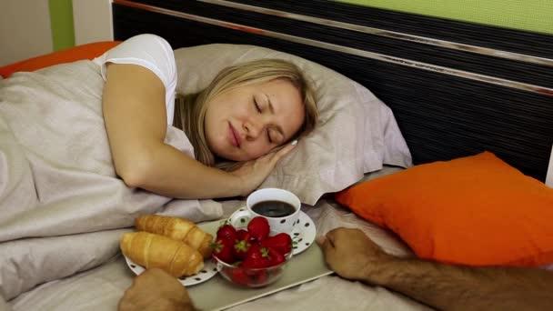 Káva v posteli. Snídaně v posteli. Croissanty, jahody a káva na snídani. Mladé páry romantická snídaně, novomanželé, novomanželé. Líbánky, mladá rodina