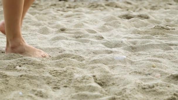 A nők lába van, a homokban. Homok, a tenger, a szép lábak. Lány séta a tengerparton.