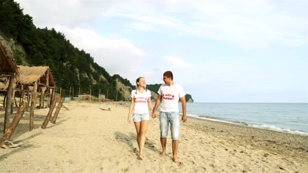 A couple walking along the beach by the sea. Newlyweds going over the sand. Man and woman at the sea. Honeymoon, romance, just married.
