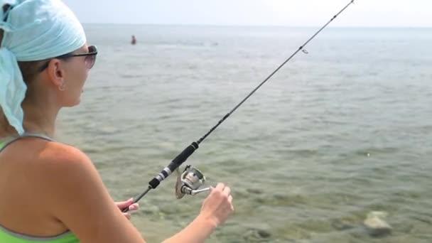 Žena s rotující chytání ryb. Mořský rybolov na spinning. Žena vyvolá předení. Fisherwomanon na moři loví s rotující.