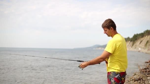 Férfi spinning gyönyörködtető hal. Ember eldobja a spinning. Tengeri halászat a fonásra. A Beach Fisherman.