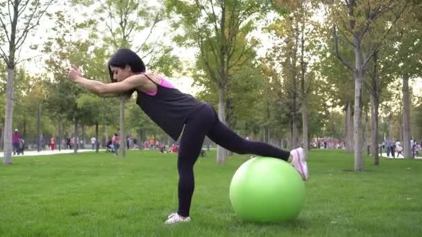 Junge Sportlerin treibt Sport und turnt im Park mit Fitnessball