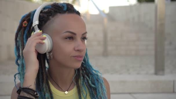Porträt einer modernen jungen attraktiven Frau mit Kopfhörern im Freien