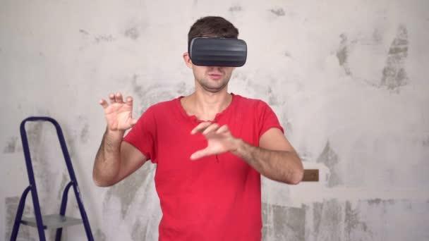 Ein Mann mit Virtual-Reality-Brille repariert und betrachtet das Innere eines neuen Hauses
