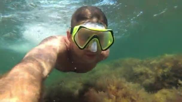 Ein junger männlicher Taucher in Maske schwimmt im Meer unter Wasser