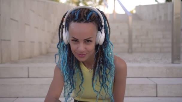 Fiatal vonzó modern nő hallgat zenét fejhallgatóval a szabadban