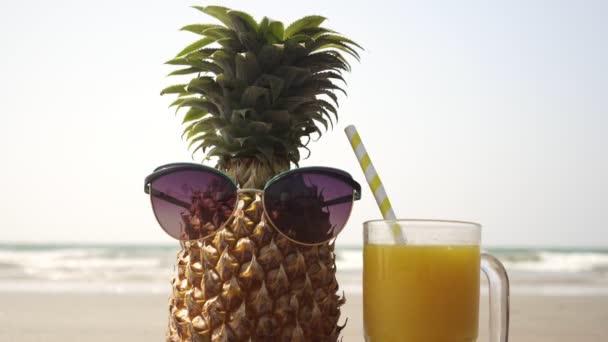 Vicces ananász napszemüvegben, egy pohár lével a tenger hátterében.