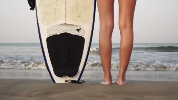 Young woman stands with a surfboard on the sandy sea coast