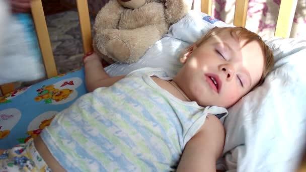 spící dítě pokryté přikrývky do postýlky