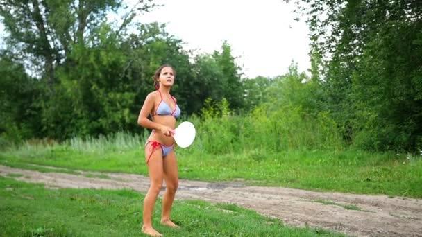 dívka v plavkách hrát tenis venku