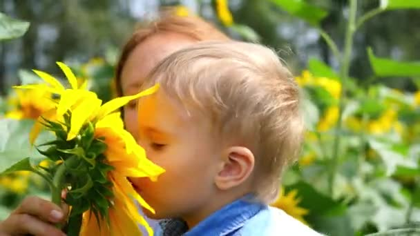 the child in his mothers arms playing with flower