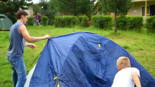 a man with kids gathering tent