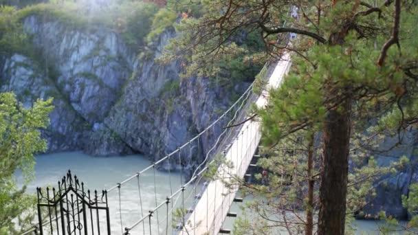 lidé přes visutý most