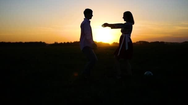 Milovníci kluk s holkou objímání při západu slunce