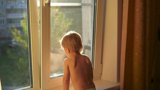 dítě se dívá na otevřené okno
