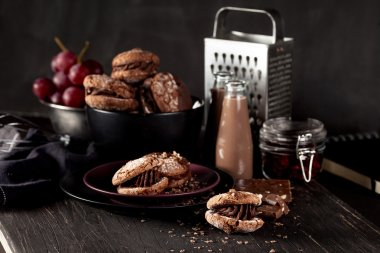 Almond cookies and chocolate milkshake on dark wooden background